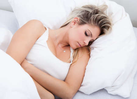 pms: Portrait of woman with stomach ache lying on bed