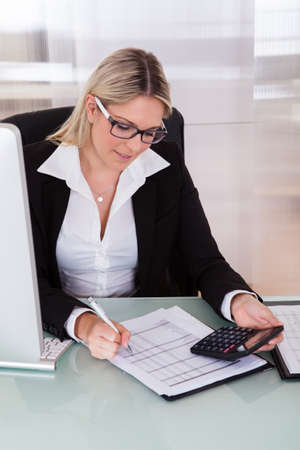 account executives: Young Businesswoman Calculating Data In Her Office