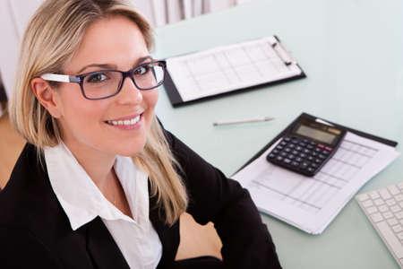 彼女のオフィスでデータを計算する若い実業家