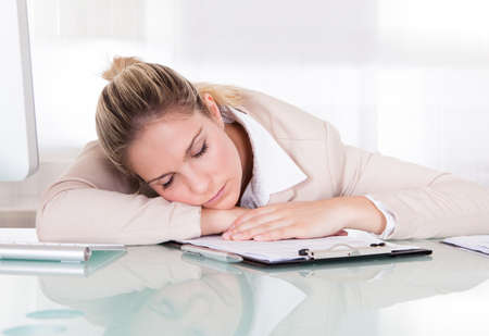 Exhausted Young Businesswoman Sleeping At Her Workplace photo