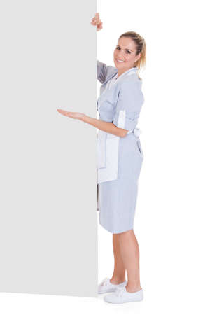 Young Maid Gesturing On Blank Placard Over White Background photo