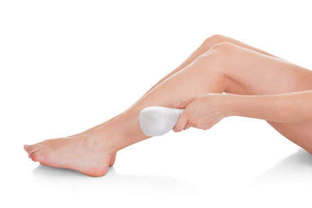 hair part: Close-up Of Woman Doing Leg Laser Treatment Over White Background Stock Photo