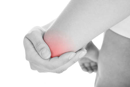 Close up of woman with elbow pain isolated on white background photo