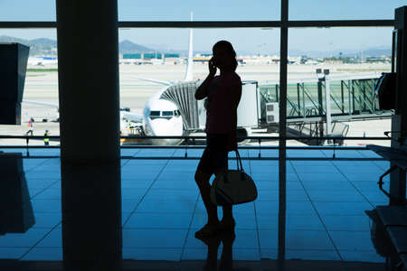 Silhouette of women talking on cell phone in airport terminal photo