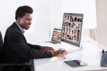 Portrait Of Happy Professional Businessman Editing Images In Office photo