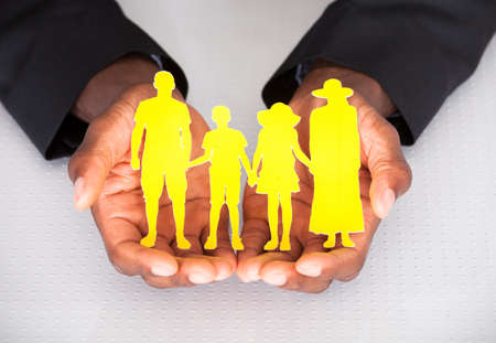 Close-up Of Male Hand Holding Family Cutout Shape photo