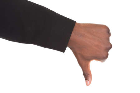 Close-up Of An Businessmans Hand Showing Thumb Down Sign Isolated Over White Background photo