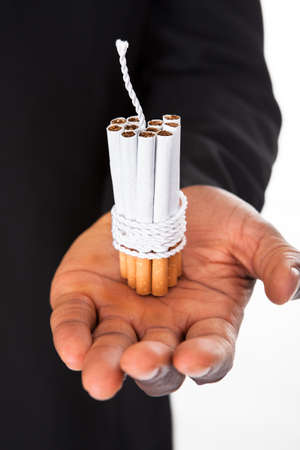 Close-up Of Human Hands Holding Cigarettes Tied With Rope And Wick photo
