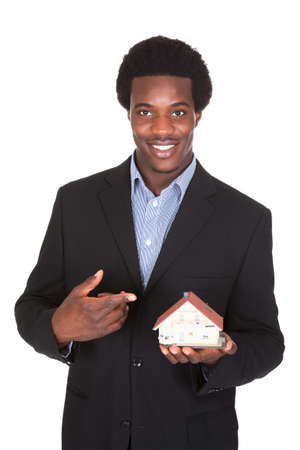 hands holding house: Young African Businessman Holding House Model Isolated Over White Background