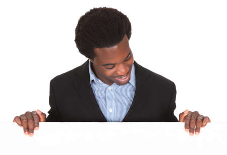 Happy African Businessman Standing On White Background Looking At Placard Stock Photo - 21329507