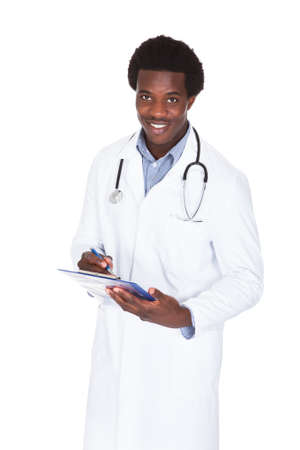 Portrait Of A Happy Male African Doctor Writing On Clipboard photo