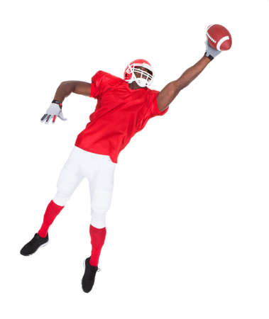 Portrait Of American Football Player Catching Rugby Ball Over White Background photo