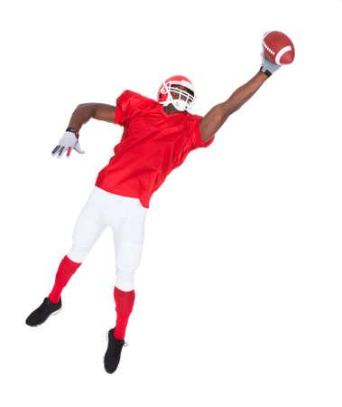 casco rojo: Retrato de Jugador de fútbol americano Atrapar Pelota de rugby sobre el fondo blanco Foto de archivo