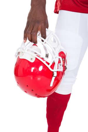 casco rojo: Primer Plano De africano Jugador de fútbol americano que sostiene el casco rojo
