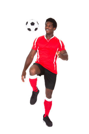 Portrait Of African Soccer Player Kicking Football Over White Background Banco de Imagens