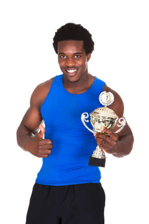 Portrait Of Happy African Athlete Over White Background Holding Trophy photo