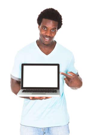 Boldog fiatal afrikai férfi használata laptop elszigetelt fölött fehér háttér