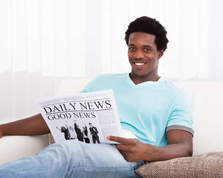 happy young man: Portrait Of Casual Young African Man Reading Newspaper Sitting On Couch Stock Photo