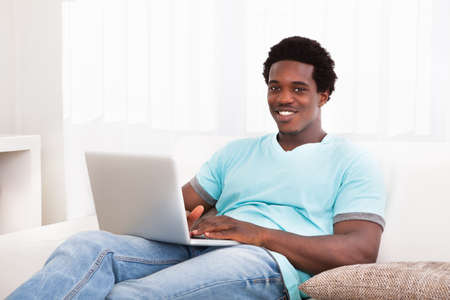 Happy Young African Man Using Laptop Sitting On Couch At Home Stock Photo - 21329563