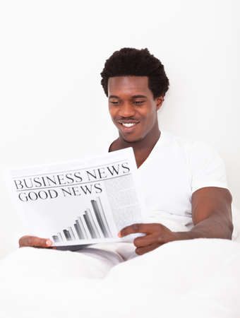 Portrait Of Casual Young African Man Reading Newspaper Sitting On Bed photo