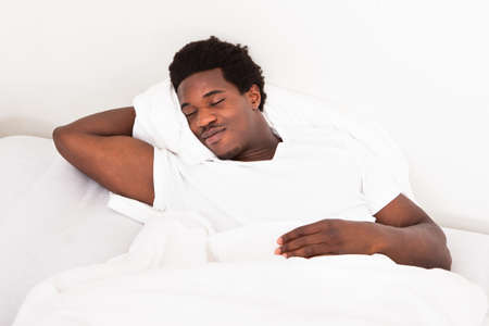 american content: Handsome Young African Male Sleeping In Bed At Home