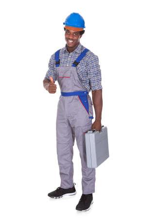Portret Van Een Jonge Afrikaanse Ambachtsman die Zijn Duim Omhoog Op Witte Achtergrond Stockfoto