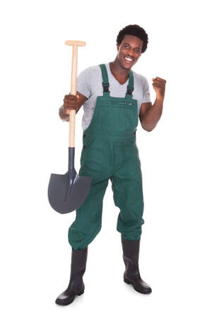 Happy Male Gardener Holding Shovel Over White Background photo