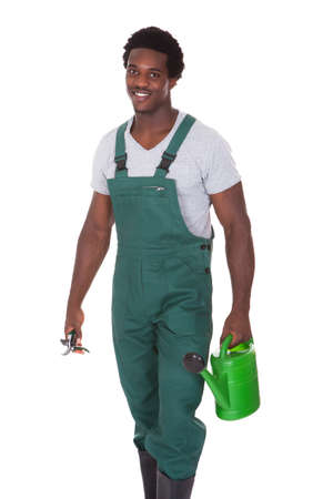 agricultural tools: Happy Male Gardener Holding Watering Can And Pliers Over White Background Stock Photo