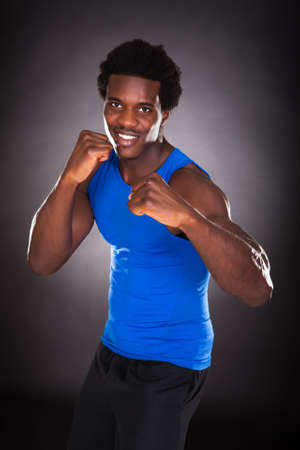 individual sport: Portrait Of Young Happy African Man Over Black Background Stock Photo