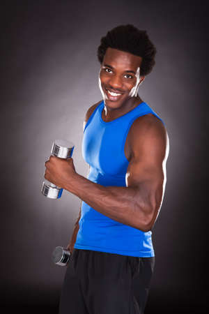 man working out: Young African Man Working Out With Dumbbells