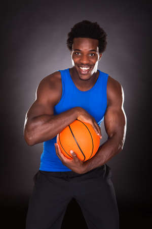 boy basketball: Young African Man Holding Basketball Over Black Background Stock Photo