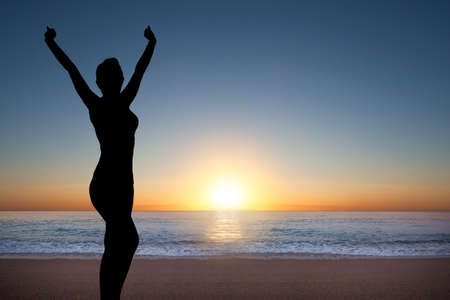 winning woman: Silhouette of happy woman during sunrise at the sea Stock Photo