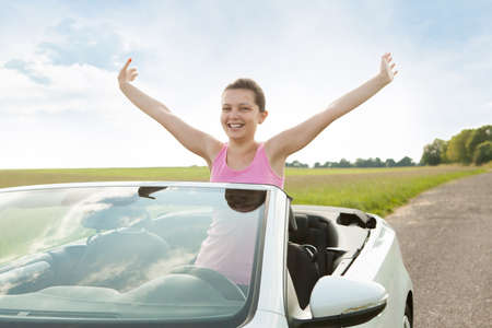 cabrio: Happy Woman Raising Hand In Car While Travelling