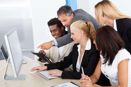 trabajo en la oficina: Empresario Mostrando en el ordenador a sus colegas Foto de archivo