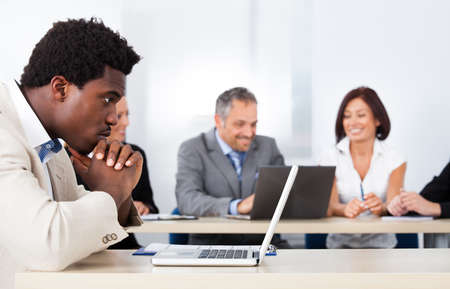 contemplated: Contemplated African Businessman Looking At Laptop In Front Of Colleagues Stock Photo