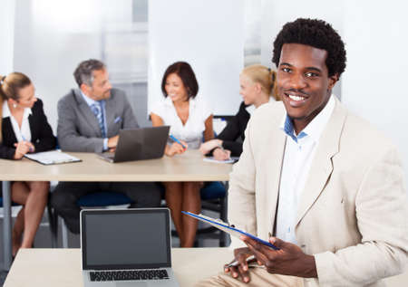 african businessman: Portrait Of Happy African Businessman Sitting In Front Of Colleagues Stock Photo