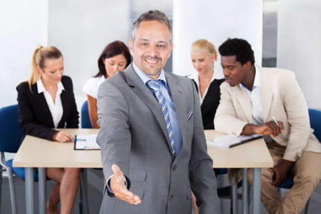 Happy Mature Businessman Extending Hand To Shake In Front Of Colleagues photo