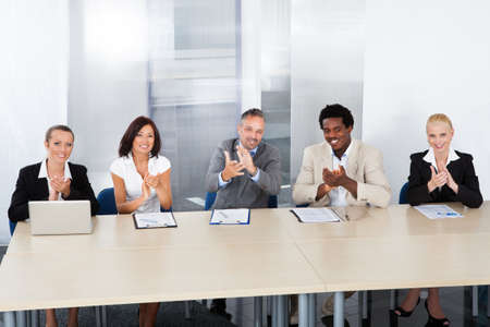 committee: Group Of Corporate Personnel Officers Applauding In Office Stock Photo
