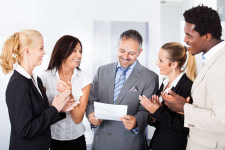 Happy Colleagues Applauding Businessman Holding Paper In Office photo