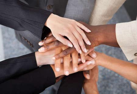 manos juntas: Vista elevada de Empresarios multirraciales apilamiento manos una sobre la otra