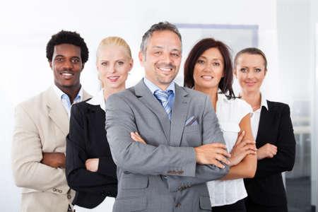 A 列に並んで立って幸せの多民族のビジネスマンのグループ