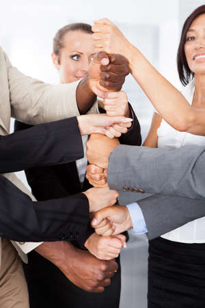 Close-up Of Multiracial Businesspeople Stacking Fist Over Each Other photo