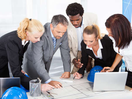 workplace safety: Group Of Happy Multiracial Businesspeople Discussing Together In Office