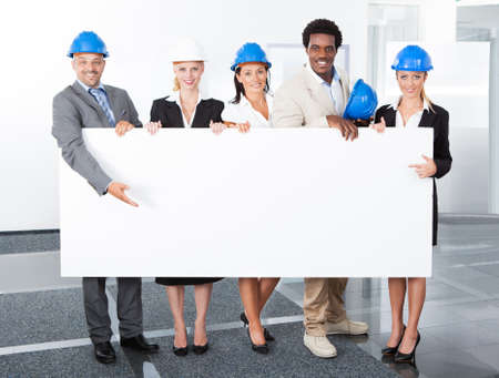 Group Of Happy Multiracial Architects Holding Placard In Office photo