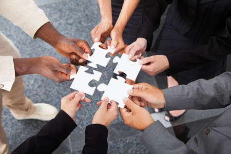 Close-up Photo Of Businesspeople Holding Jigsaw Puzzle photo