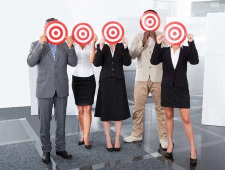 Group Of Businesspeople Holding Dartboard In Front Of Face photo
