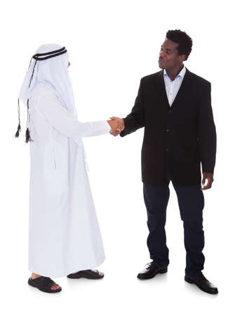 Arabic And African Man Shaking Hands Over White Background photo