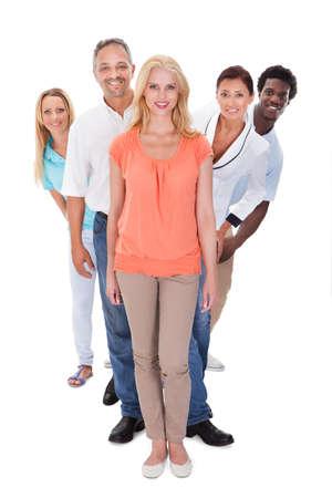 file d attente: Groupe de personnes multi-raciales permanent dans une rangée sur fond blanc