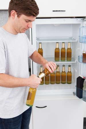 tomando refresco: Joven de pie al lado de la nevera y la apertura de la cerveza