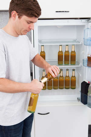 Young man standing beside the refrigerator and opening beer photo